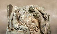 "Close up of a Roman Sebasteion relief  sculpture of Io and Argos Aphrodisias Museum, Aphrodisias, Turkey.  Against an art background.<br /> <br /> A powerful hero is folding a sword gazing closely at a half naked and dishevelled young heroine who sits on a chest like stool. Between, on a pillar base stood a small, separately added statue of a goddess ( now missing). The scene follows a scheme used in the relief panels ""Io guarded by Argos"". Io was one of Zeus's lovers, and Argos was a watchful giant sent to guard her by Hera, Zeus's wife."