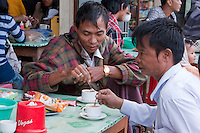 Myanmar, Burma, Shan State.  Two Burmese Men having Coffee at a Roadside Rest Stop.