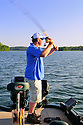 00416-028.17 Fishing: Angler is doing two hand cast from boat.  Muskie, pike.
