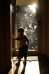 My older son, age two, stands in the doorway of on a summer evening.