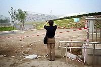 """CHINA. Beijing. A tourists taking a picture of the new Olympic park. In recent years construction has boomed in Beijing as a result of the country's widespread economic growth and the awarding of the 2008 Summer Olympics to the city. For Beijing's residents however, it seems as their city is continually under construction with old neighborhoods regularly being razed and new apartments, office blocks and sports venues appearing in their place. A new Beijing has been promised to the people to act as a showcase to the world for the 'new' China. Beijing's residents have been waiting for this promised change for years and are still waiting, asking the question """"Where's the new Beijing?!"""". 2008"""