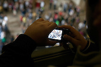 A person takes a picture of crowds in Lobby 7 before a flashmob danced at noon in the room during the MIT Under the Dome open house in Cambridge, Massachusetts, USA.