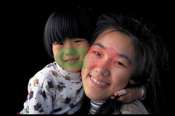 portrait of smiling young woman holding toddler girl