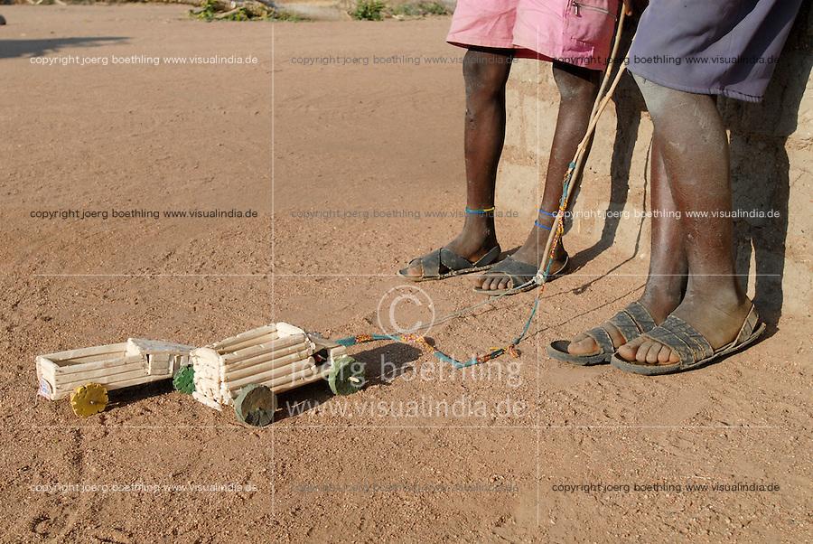 TANZANIA, Meatu, young boys with toy cars and sandals from car tyre in village / TANSANIA Meatu , Jungen mit Sandalen aus Autoreifen und selbstgebauten Spielautos in einem Dorf