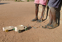 TANZANIA, Meatu, young boys with toy cars and sandals from car tyre in village / TANSANIA Meatu , Jungen mit Sandalen aus Autoreifen und selbstgebauten Spielautos in einem Dorf