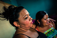 Salvadoran sex workers look at the bar's entrance while waiting for clients in a street sex club in San Salvador, El Salvador, 7 April 2018. Although prostitution is not legal in El Salvador, dozens of street sex workers, wearing provocative miniskirts, hang out in the dirty streets close to the capital's historic center. Sex workers of all ages are seen on the streets but a significant part of them are single mothers abandoned by their male partners. Due to the absence of state social programs, they often seek solutions to their economic problems in sex work. The environment of street sex business is strongly competitive and dangerous, closely tied to the criminal networks (street gangs) that demand extortion payments. Therefore, sex workers employ any tool at their disposal to struggle hard, either with their fellow workers, with violent clients or with gang members who operate in the harsh world of street prostitution.