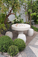 Chess game table and stool seats in backyard patio with buxus boxwood, cornus kousa, in Oriental Japanese Asian Chinese styled garden design with pebbled walk