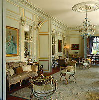 In the main drawing room a gilt-framed portrait of the Duchess of Windsor hangs above a sofa flanked by an Empire armchair and stool