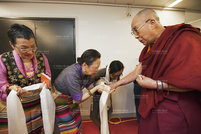 "Switzerland. Basel. St. Jakobshalle. Dolma Knell (L), Yangchen Büchli (C) and Dicki Shitsetsang (R) greet and pay tribute to His Holiness the Dalai Lama. They offer him scarfs, called khata, with a humble bow before them, with head bent over and palms joined in respect. In most cases the giver will receive his or her Khata back from the given, as a token of blessing back to them. When a Khata is offered to His Holiness the Dalai Lama and received back, it will be cherished and preciously kept as it is now a very special blessing, a talisman and protector. The three women are part of Aeschimann's children who arrived 50 years ago in Switzerland to receive custody on a private initiative by an influential Swiss industrialist, Charles Aeschimann. Yangchen Büchli (C) holds in her hand an old black and white picture shot before her departure and depicting her as child with the young Dalai Lama. In 1962, Charles Aeschimann agreed with the Dalai Lama to take 200 children and place them in Swiss foster homes and give them a chance for a better life and a good education. Most of the children still had parents in exile or in Tibet, just a few were orphans. The 14th and current Dalai Lama is Tenzin Gyatso, recognized since 1950. He is the current Dalai Lama, as well as the longest-lived incumbent, well known for his lifelong advocacy for Tibetans inside and outside Tibet. Dalai Lamas are amongst the head monks of the Gelug school, the newest of the schools of Tibetan Buddhism. The Dalai Lama, also called "" Ocean of Wisdom"" is considered as the incarnation of Chenresi, the Bodhisattva of compassion who is also the protective deity of Tibet. 8.02.2015 © 2015 Didier Ruef"