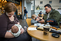 A mother breastfeeds her baby while the dad helps their older son with his drink in a museum cafe.<br /> <br /> London, England, UK<br /> 08/03/2015<br /> <br /> © Paul Carter / wdiip.co.uk