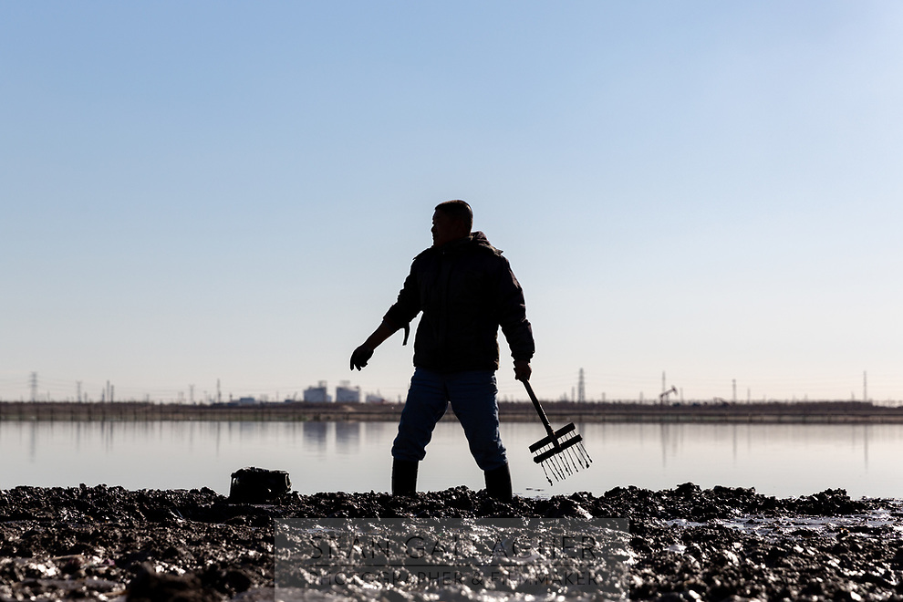 A man harvests clams from the riverbed at low tide in downtown Tianjin. Coastal erosion is already a severe problem for much of the low lying land in the region and is predicted to get worse as climate change impacts continue to intensify. 2019