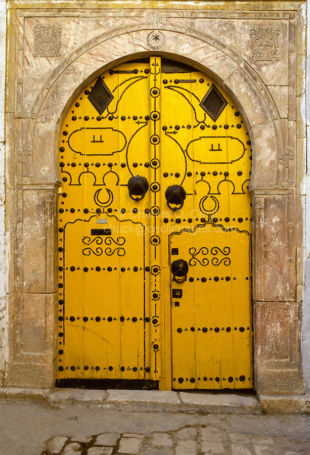 Tunisia.  Tunis Medina.  Decorated Door.  The high door knockers date from the era when guests arrived on horseback.