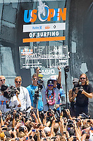 American Brett Simpson hoisting the $100,00.00 check in victory during the final day of the 2010 US Open of Surfing in Huntington Beach, California on August 8, 2010.