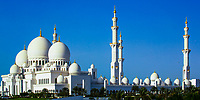 Beautiful Sheikh Zayed Grand Mosque panorama with the white domes and minarets under a blue sky, with palm trees in the foreground, in Abu Dhabi Asia
