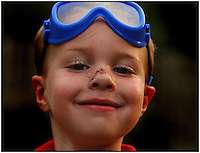 A young boy gets a dusting of dirt on his knows while playing in the garden. Image is model released.