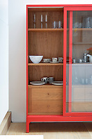 A red Joyce cabinet by Russell Pinch displays a collection of ceramics and glassware