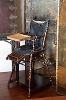 An antique highchair stands beside a hand-painted screen in the dining room