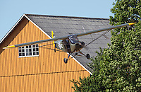 Piper L-18C Super Cub LN-ACJ coming in to land in a field near a farm.<br /> <br /> Airplanes and reenactors photographed at in connection with Høytorptreffet, an annual event at the Høytorp fort. <br /> <br /> Høytorp fort is a barrage fort in the Glomma defence line, built 1912-17. On April 13th and 14th 1940 the fort was in combat against German army units . It is now protected as a national monument.<br /> <br /> ©Fredrik Naumann/Felix Features