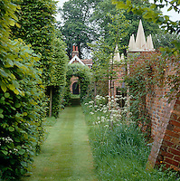A grass pathway between a red brick wall and a beech hedge leads down to an overgrown archway