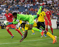 NASHVILLE, TN - JULY 3: Andre Blake #1 goes down over Elvis Powell #5 after a save during a game between Jamaica and USMNT at Nissan Stadium on July 3, 2019 in Nashville, Tennessee.