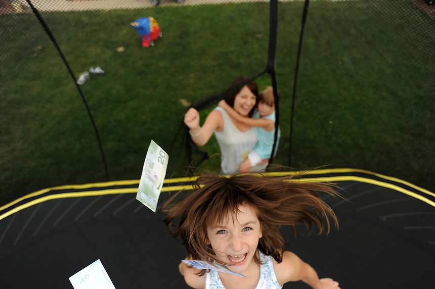 Tenille Lafontaine's daughter Nevaeh, centre, bounces on her trampoline with play money after a financial literacy lesson with her sister, Everleigh. MARK TAYLOR FOR THE GLOBE AND MAIL.