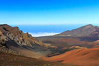A hiker's look into and out of Haleakala's massive crater on Maui reveals a surreal scenery of red swirls and rocks descending into the clouds below.