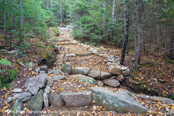 Mt Tecumseh Trail in the Waterville Valley, New Hampshire in September 2011. Trail stewardship groups suggest that only needed stone structures that benefit the trail should be built along a trail and that the best maintained trails will have stonework that looks natural. The row of rocks on the right may be to discourage hikers from going around the steps, but it is unneeded. Using brush and dead trees to block that side would be the better option, and it would look natural. It is believed this section of stonework was built in 2011.