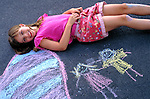 smiling young girl making art on sidewalk in park