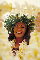 Native Hawaiian woman in traditional attire welcoming tourist to the island with the gift if a lei.