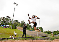 A young girl jumps into the air while participating in a long jump competition at a track and field event.