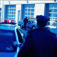 Policemen approaching white building<br />