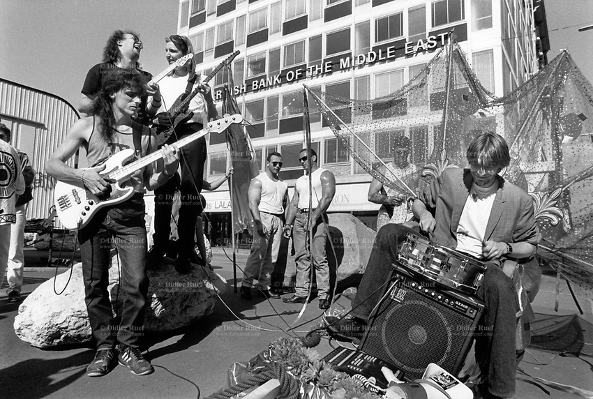 Switzerland. Geneva. A band is playing music in the streets on Music Day. Drums, guitar and bass players. Two muscular men stand in the background. Bank of the Middle east. The Fête de la Musique, also known in English as Music Day, Make Music Day or World Music Day, is an annual music celebration that takes place on 21 June ( but usually during the previous or following weekend). On Music Day the citizens of a city or country are allowed and urged to play music outside in their neighborhoods or in public spaces and parks. Free concerts are also organized, where musicians play for fun and not for payment. 22.06.1993 © 1993 Didier Ruef