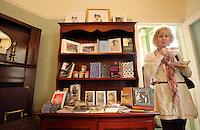 Swansea, UK. Saturday 25 October 2014<br /> Pictured: A woman enjoys a traditional 1914 afternoon tea by a bookcase filled with books, leaflets and other printed material at the house where Dylan Thomas was born.<br /> Re: Dylan Thomas birthday centenary celebrations at his birthplace, 5 Cwmdonkin Drive, Swansea, south Wales.