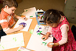 Education elementary Kindergarten art activity drawing with markers boy and girl working at table horizontal
