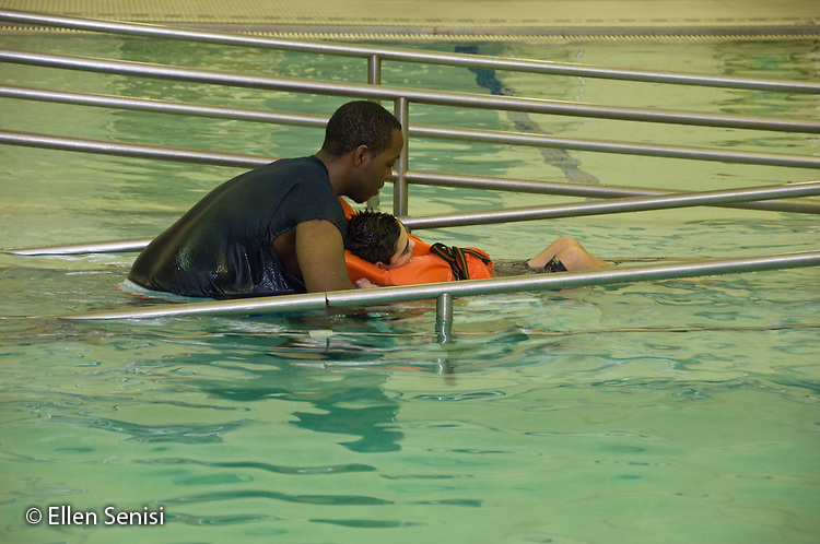 MR/Albany.Langan School at Center for Disability Services (private nonprofit disability services).Upper elementary classroom/Day Program.Teaching assistant wheels student out of swimming pool after swim class. Students in this class swim once a week as part of their physical education program. Boy: 11, cerebral palsy, expressive and receptive language delays.MR: Bro12, Woo2.© Ellen B. Senisi