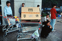 China. Province of Zhejiang. Hangzhou. Women and men outside the Carrefour supermarket and shopping center. The man, sitting his knees bent down in the traditional chinese, has just bought a new digital TV set. © 2004 Didier Ruef