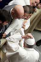 Papa Francesco posa sul capo una papalina donata da una bambina al termine dell'Udienza Generale del mercoledi' in aula Paolo VI, Citta' del Vaticano, 14 dicembre 2016.<br /> Pope Francis puts on a skull-cap given to him by a child at the end of his weekly general audience in Paul VI Hall at the Vatican, on December 14, 2016.<br /> on December 14, 2016.<br /> UPDATE IMAGES PRESS/Isabella Bonotto<br /> <br /> STRICTLY ONLY FOR EDITORIAL USE