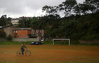 A man rides his bike across a football pitch with little grass on in Sao Paulo, one of the 12 host cities of the 2014 FIFA World Cup