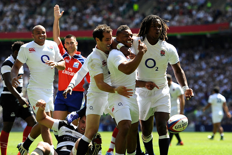 Kyle Eastmond of England is congratulated by Haydn Thomas (left) and Marland Yarde (right) after scoring on his debut during the match between England and Barbarians at Twickenham on Sunday 26th May 2013 (Photo by Rob Munro)