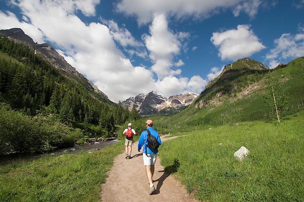 Two Caucasian men hiking along Maroon Creek towards the Maroon Bells Peaks, Aspen, Colorado, USA