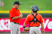 Frederick Keys manager Ryan Minor (53) talks with catcher Allan de San Miguel (11) after making a pitching change during the Carolina League game against the Winston-Salem Dash at BB&T Ballpark on May 28, 2013 in Winston-Salem, North Carolina.  The Dash defeated the Keys 17-5 in the first game of a double-header.  (Brian Westerholt/Four Seam Images)