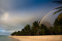 Beautiful double rainbow on Le Morne Brabant mountain, from a coconut tree white sand beach under a tropical shower, in Mauritius Island, Africa