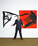 """Miami Art Museum director Thom Collins photographed at MAM with Anna Maria Maiolino's """"Untiltled, from 'Acoes Matericas' series"""""""