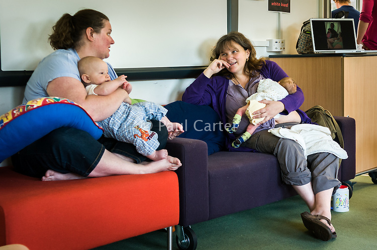 A mother breastfeeds her baby while talking to a friend at a breastfeeding support drop-in centre.<br /> <br /> Taken - 27/04/2011<br /> Hampshire, England, UK