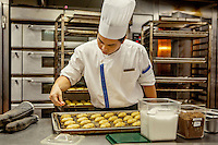 A chef in the kitchen of the Marina Bay Sands resort hotel.  The kitchen prepares Western, Chinese and Halal food simultaneously in three different sections.