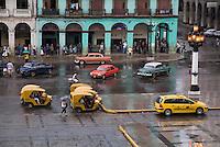 Traffic on a rainy day near the El Capitalio building in Havana, Cuba.