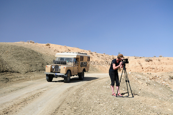 Africa, Tunisia, nr. Saket. Desert traveller Heike setting the video camera up. --- No releases available, but releases may not be needed for certain uses. Automotive trademarks are the property of the trademark holder, authorization may be needed for some uses.  --- Info: Image belongs to a series of photographs taken on a journey to southern Tunisia in North Africa in October 2010. The trip was undertaken by 10 people driving 5 historic Series Land Rover vehicles from the 1960's and 1970's. Most of the journey's time was spent in the Sahara desert, especially in the area around Douz, Tembaine, Ksar Ghilane on the eastern edge of the Grand Erg Oriental.