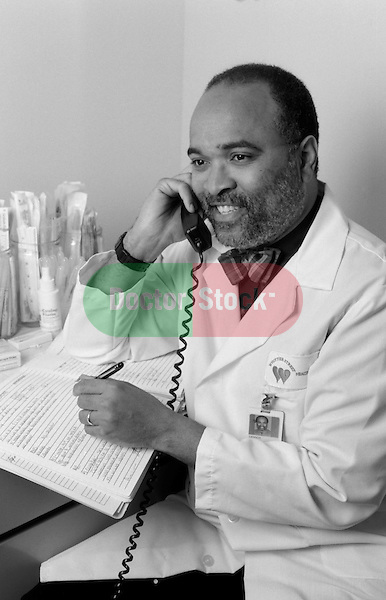 b/w image of African American doctor on telephone in office