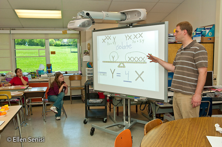 MR / Schenectady, New York. Zoller Elementary School (urban public school). 5th grade inclusion classroom. One of a series of photographs of a math lesson where students use an electronic interactive whiteboard and individual manual whiteboard slates to visualize and comprehend algebraic equations. Teacher uses interactive whiteboard to visually represent the equation. MR: Yau5. ID: AJ-g5y © Ellen B. Senisi