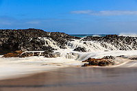 Waves crash over and filter through volcanic rock before returning to the sea, Lumaha'i Beach, Kaua'i.